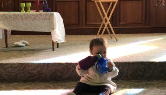 Infant sits on the floor pretending to pour wine